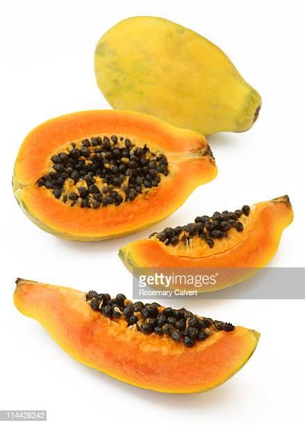 Two fresh, ripe papaya fruits one sliced through.