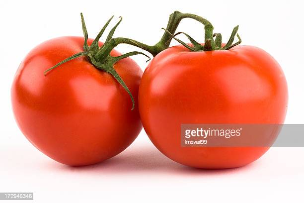 Two fresh ripe tomatoes isolated on white background