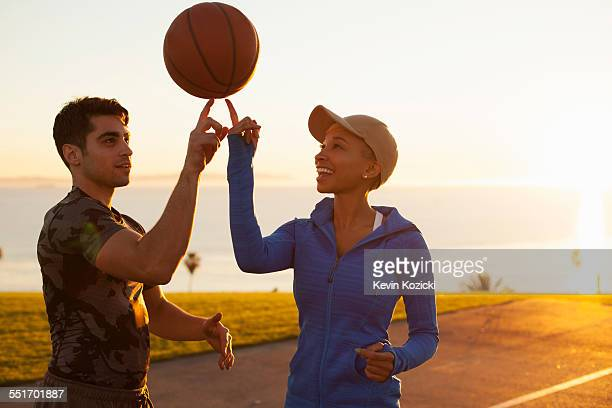 Two friends balancing basketball on their finger