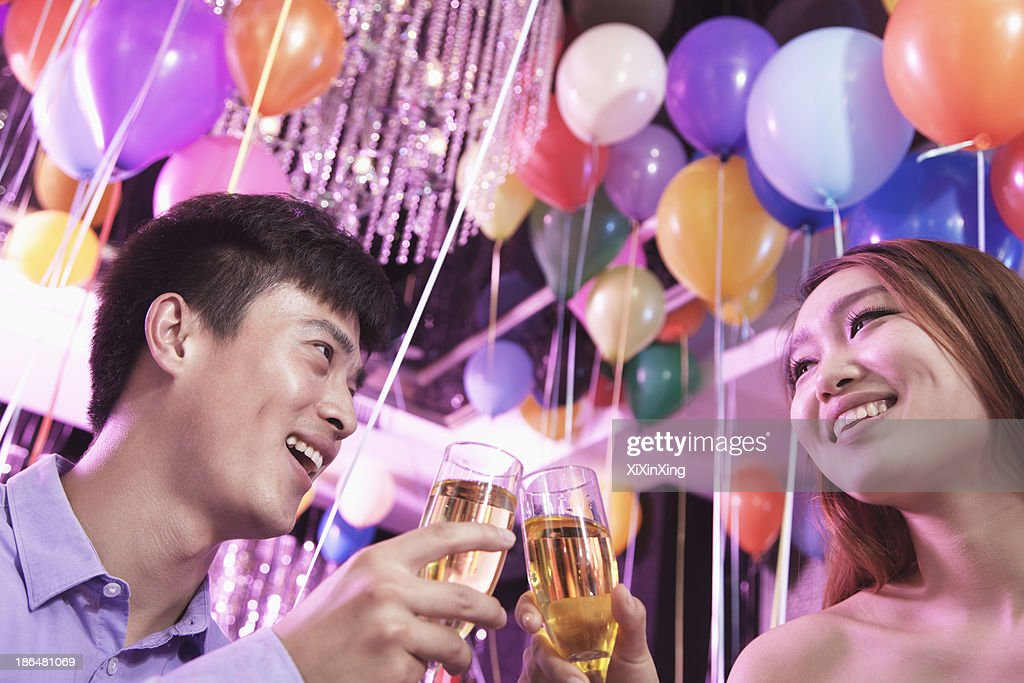 Two friends celebrating, toasting with champagne, nightclub in Beijing, balloons in the background : Stock Photo