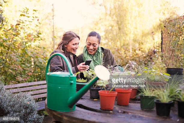 Two friends checking a phone while gardening