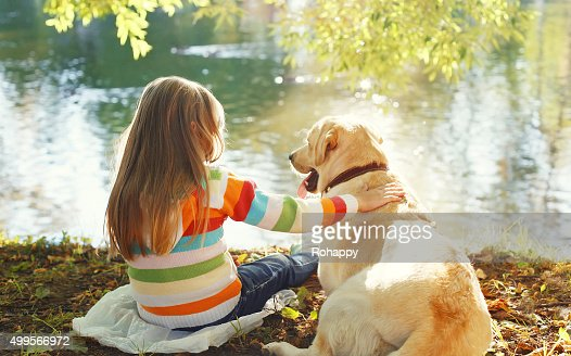 Two friends, child with Labrador retriever dog sitting in sunny : Stock Photo