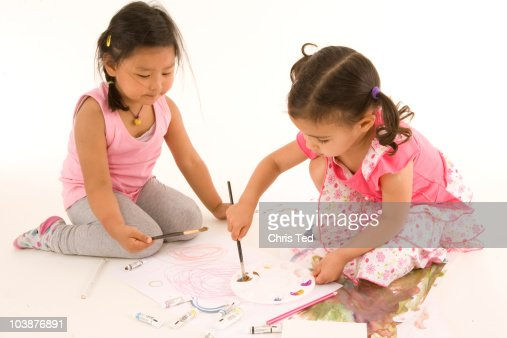 two friends drawing and painting on paper : Stock Photo
