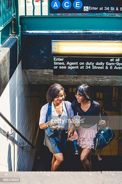 Two friends drinking iced coffee out of the subway