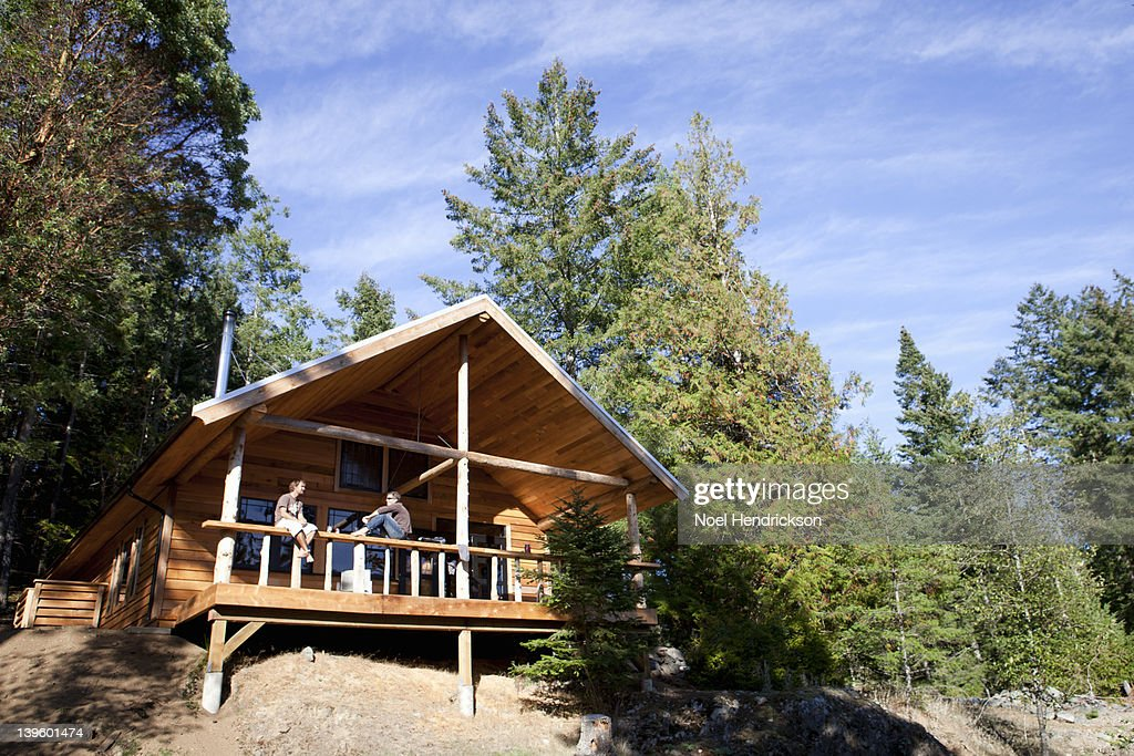 Two Friends Hang Out On A Cabin Patio : Stock Photo