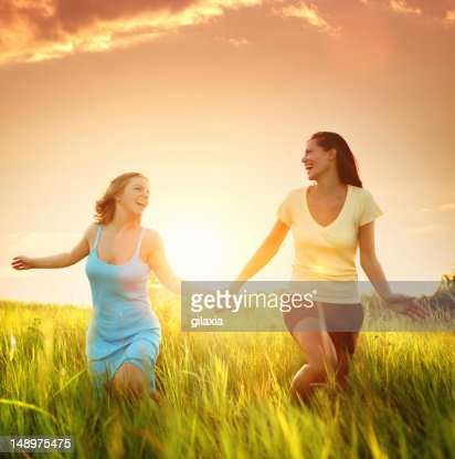 Two friends happily running through grass : Stock Photo