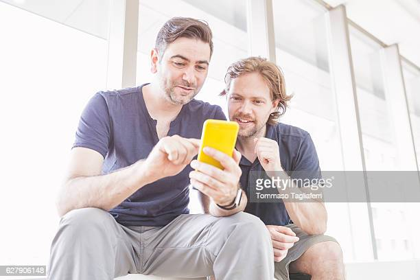 Two friends have fun watching something on smart phone