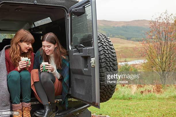 Two friends having tea in the back of their car