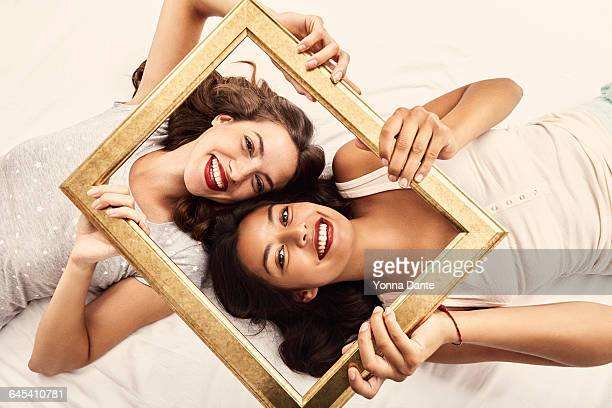 two friends holding a golden frame