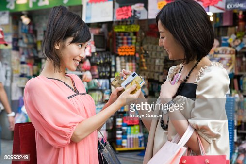 Two friends holding credit cards