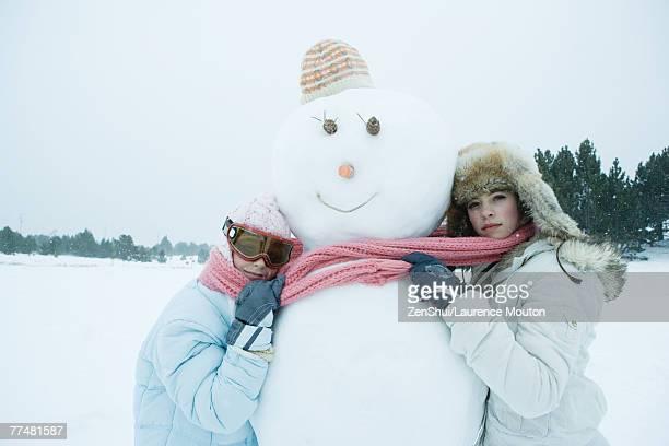 Two friends hugging snowman
