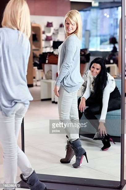 two  friends  in department store looking at new shoes