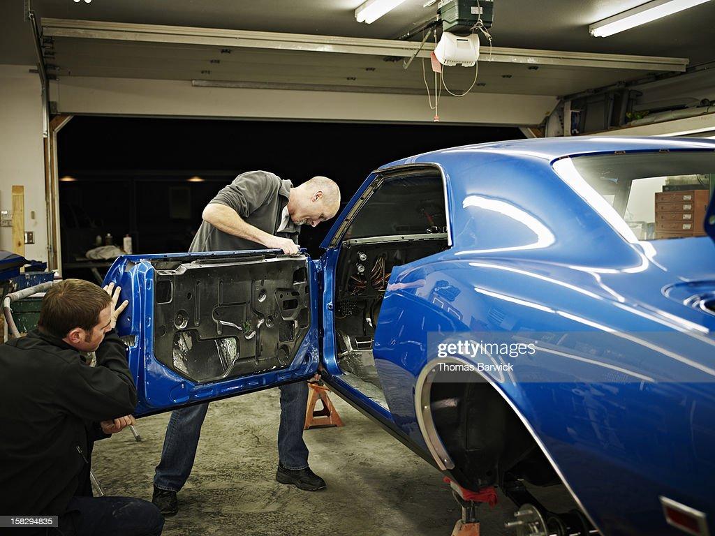 Two friends in garage installing door on car : Stock Photo