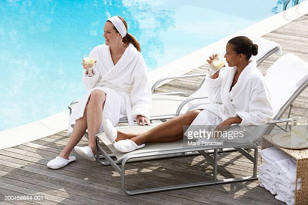 Two friends in robes drinking near pool, side view