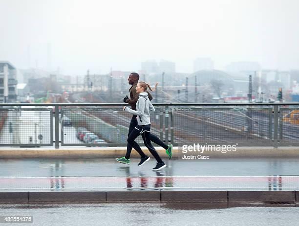 two friends jogging across urban street bridge
