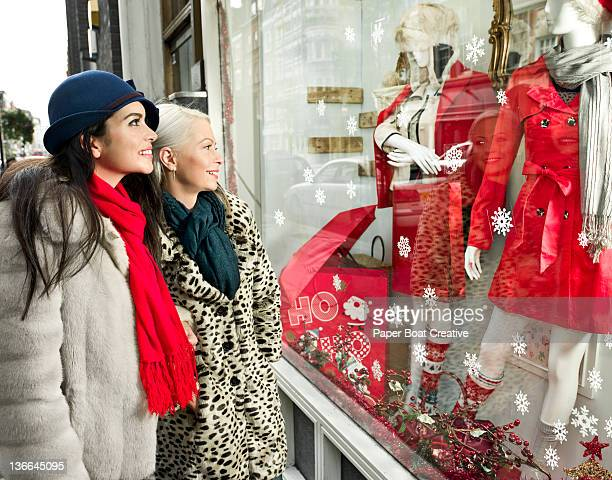 two friends looking at a Christmas shop window
