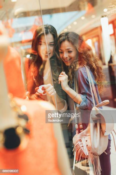Two friends looking at a dress in a clothing store