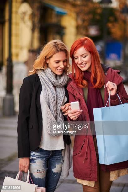 Två vänner tittar på mobiltelefonen
