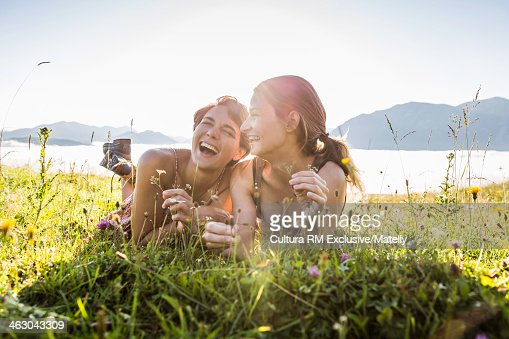 Two friends lying in field laughing, Tyrol, Austria