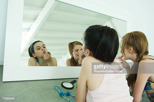 Two friends lying on floor, applying lipstick, looking at selves in mirror