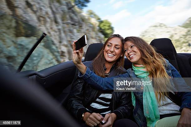 Two friends making selfie on back of car