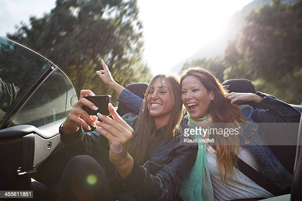 Two friends making selfie on the backseat of car
