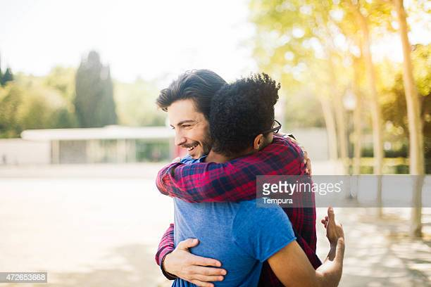 Two friends meet and hug in the streets of Barcelona.
