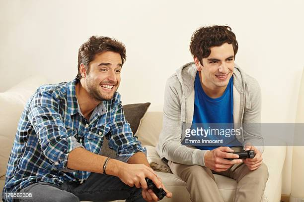 two friends on sofa playing video games
