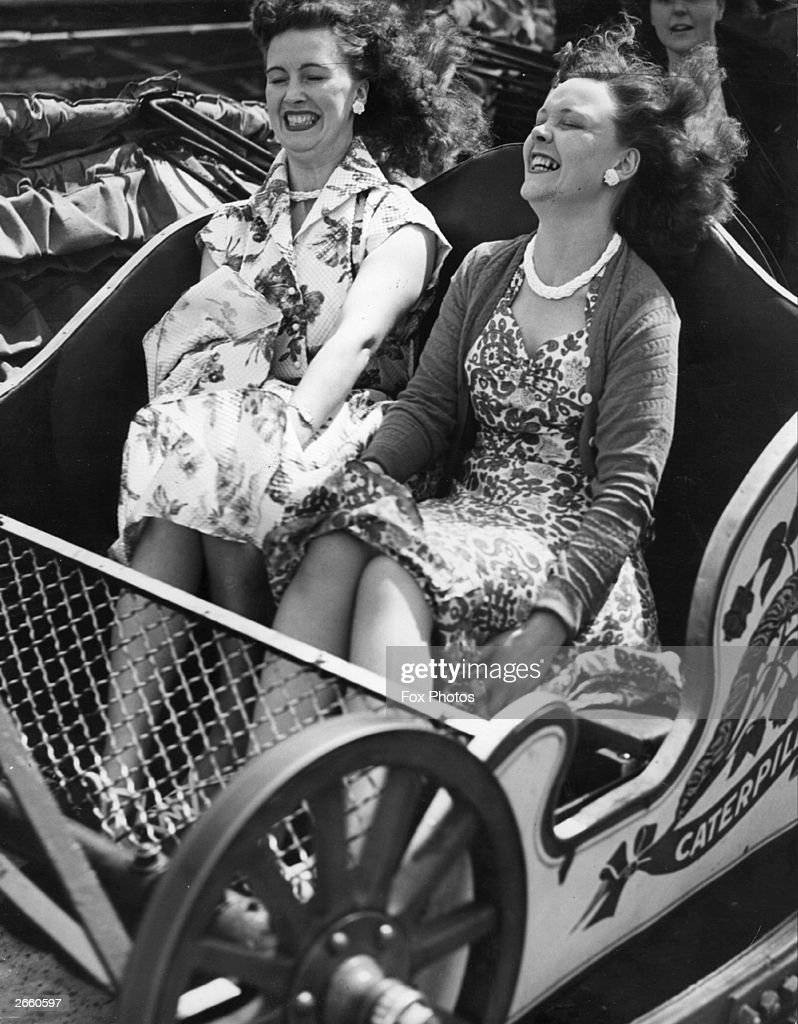 Two friends on the caterpillar ride at Southend fun fair.