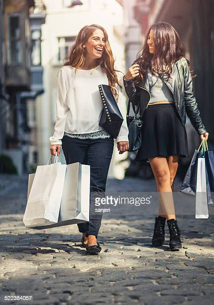Two friends on the street with shopping bags