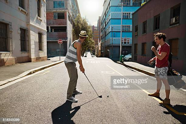 Two friends playing urban golf in the city