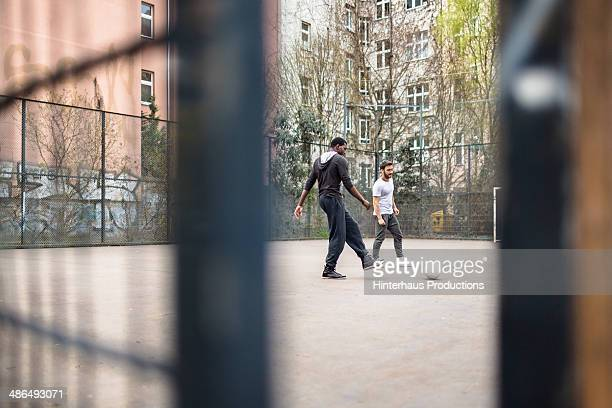 Two friends playing urban soccer