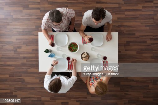 Two friends raising their glasses in a toast at a dinner party, overhead view
