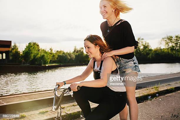 Two friends riding BMX bicycle together