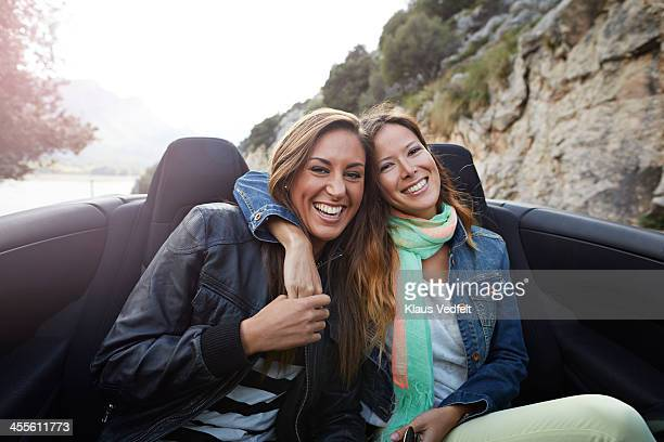 Two friends riding in the backseat of car