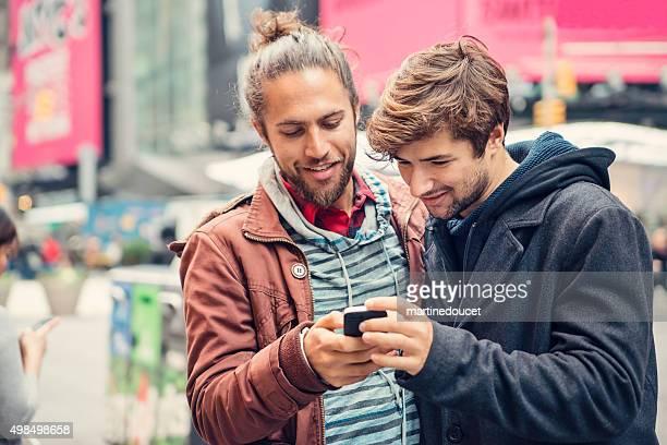 Zwei Freunde teilen auf einem Handy in der Straße in der Stadt.