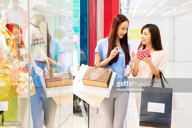 Two friends shopping with mobile phone