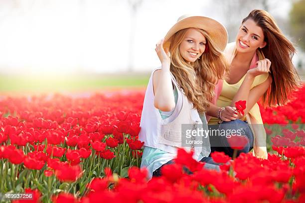 two friends sitting in the middle of tulip field