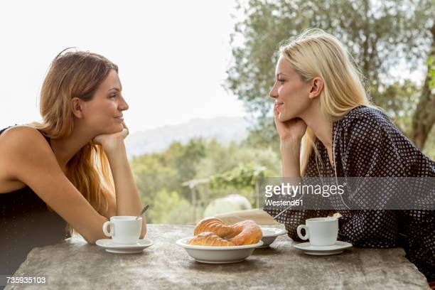 Two friends smiling at each other at breakfast table