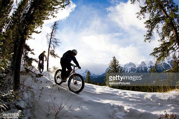 Two friends snow biking along mountain trail in the winter