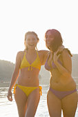 Two friends stand laughing in swimwear at dawn