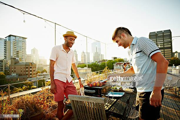 Two friends standing at barbecue on rooftop deck