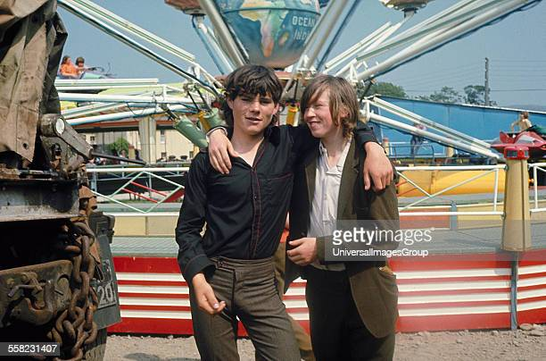 Two friends standing in front of fairground ride Puck Fair Killorglin Ireland 1973