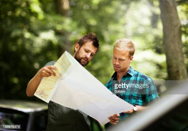 Two friends standing in nature looking at map