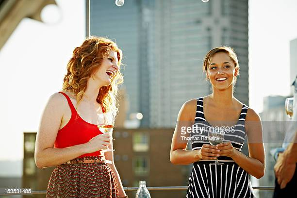 Two friends standing on rooftop deck laughing