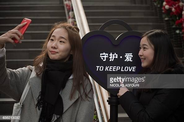 Two friends take a selfie next to a heartshaped sign that reads 'to keep love' on Valentine's Day in Beijing on February 14 2017 / AFP / NICOLAS...