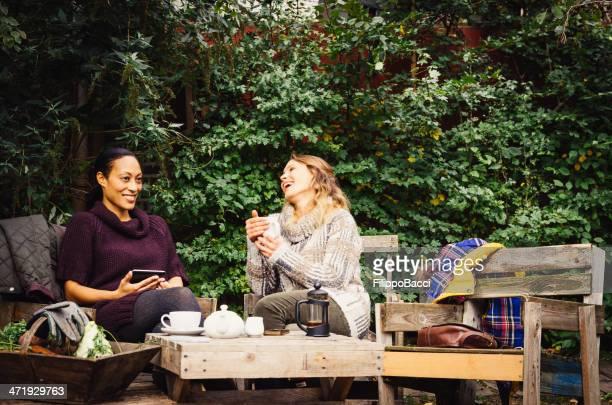 Two Friends Take Tea In The Garden