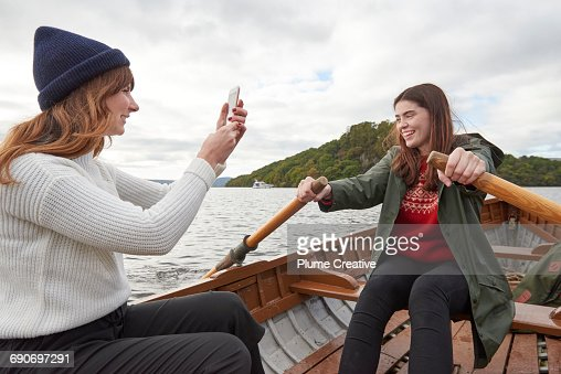 Two friends taking a photo in a row boat