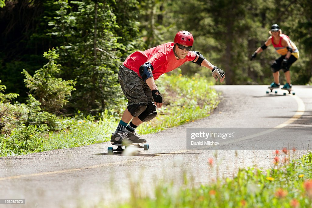 Two friends taking turns on longboards. : Stock Photo