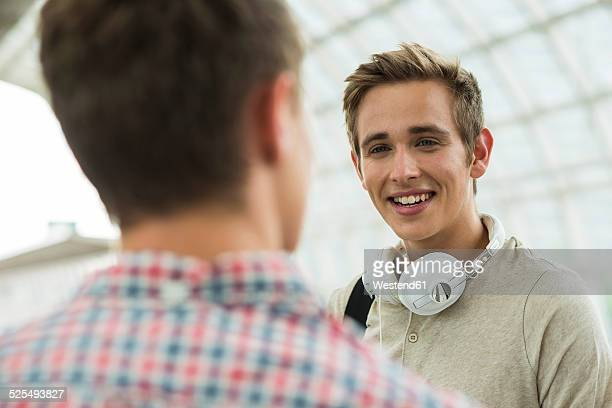 Two friends talking at commuter train station